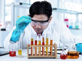 Portrait of young male scientist studying chemical liquid in the modern laboratory